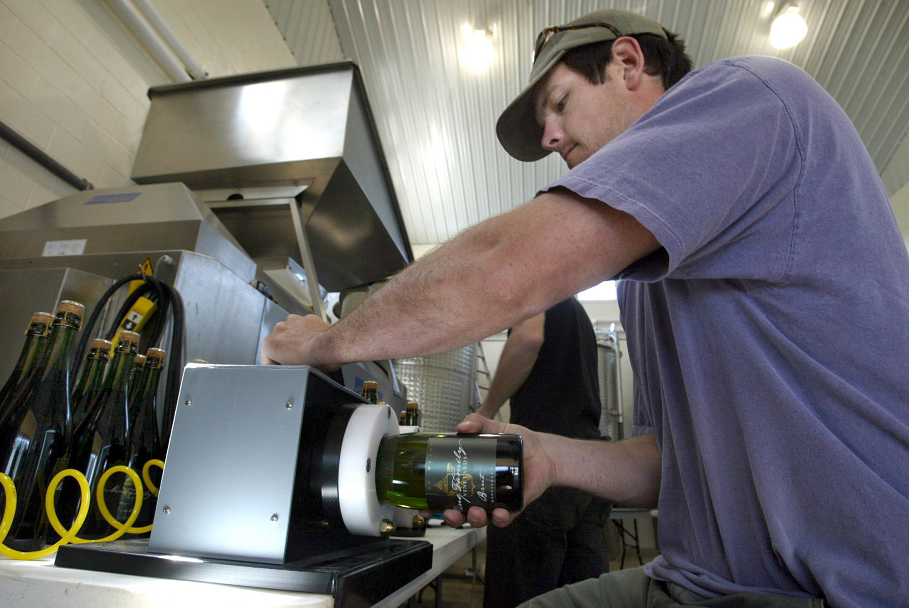 Carrington King labels a bottle of champagne in the tank room at the King Family Vineyards on Wednesday, May 7, 2008, in Crozet, Va.  Carrington's father, David King, is the owner of King Family Vineyards and the board chairman of the state-run Virginia Wine Distribution Co. The nonprofit distribution company retains the three-tier system used by a majority of states following the repeal of Prohibition in 1933 that takes the wine from the winery to the wholesaler to the retailer. (AP Photo/Lisa Billings)