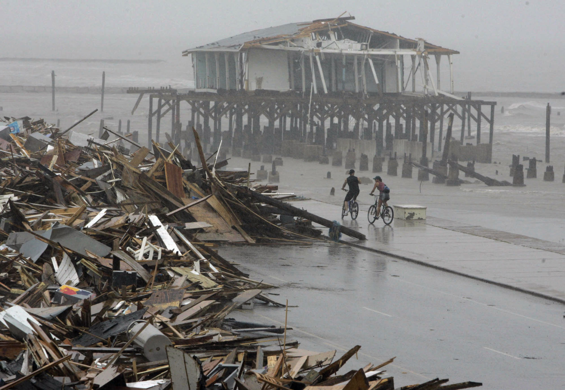 FILE - In this Sept. 14, 2008, file photo, cyclists ride past debris piled up on the seawall road after Hurricane Ike hit the Texas coast in Galveston. Most municipal recovery projects in Galveston in the wake of the hurricane have been finished in the eight years since the storm battered the island. Ike made landfall in Galveston on Sept. 13, 2008. (AP Photo/Matt Slocum, File)
