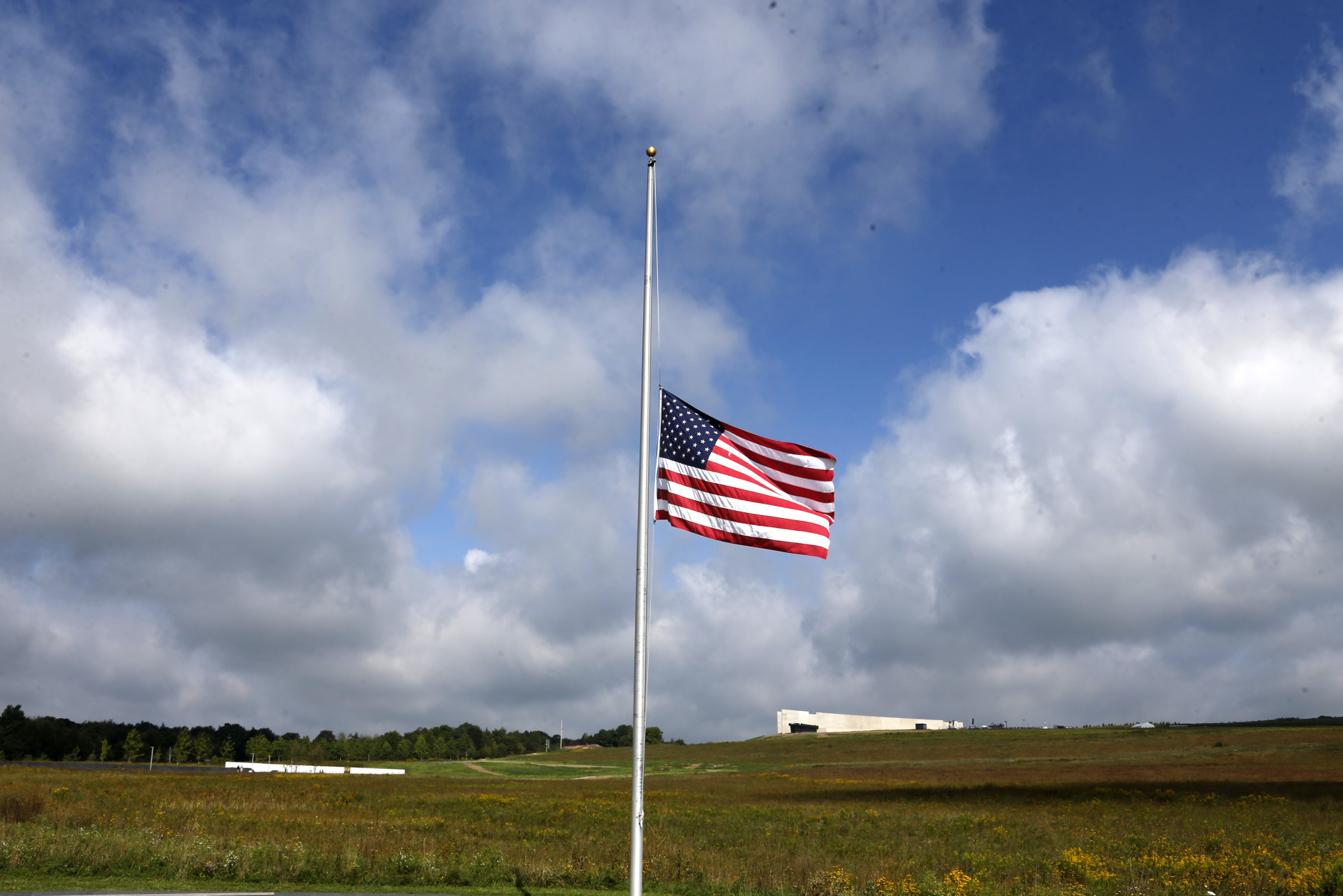 A flag flies at half staff at the Flight 93 National Memorial in Shanksville, Pa, Friday, Sept. 11, 2015, as the nation marks the 14th anniversary of the Sept. 11 attacks. At lower left is the Wall of Names,and upper right is the Flight 93 National Memorial Visitors Center. (AP Photo/Gene J. Puskar)
