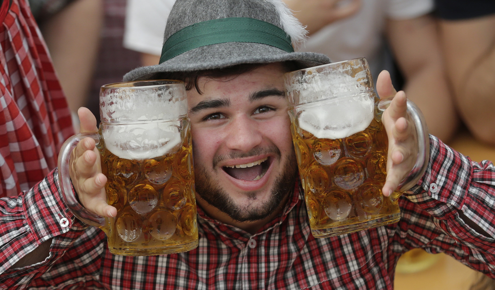 A young man poses with beer mugs at the second weekend in the 'Hofbraeuhaus beer tent' at the famous beer festival Oktoberfest in Munich, southern Germany, Sunday, Sept. 28, 2014. The world's largest beer festival will be held from Sept. 22 to Oct. 5, 2014. (AP Photo/Matthias Schrader)