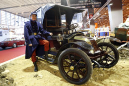 An actor dressed like a WWI soldier poses in front of a 1914 Renault AG1, known as Taxi de la Marne, during the Retromobile vintage cars exhibition, in Paris, Wednesday, Feb. 5, 2014. The exhibition runs until Friday Feb. 7, 2014. The name Taxi de la Marne was not used until the outbreak of World War I, when the fleet of Paris taxis was requisitioned by the French Army to transport troops from Paris to the First Battle of the Marne in early September 1914. (AP Photo/Jacques Brinon)
