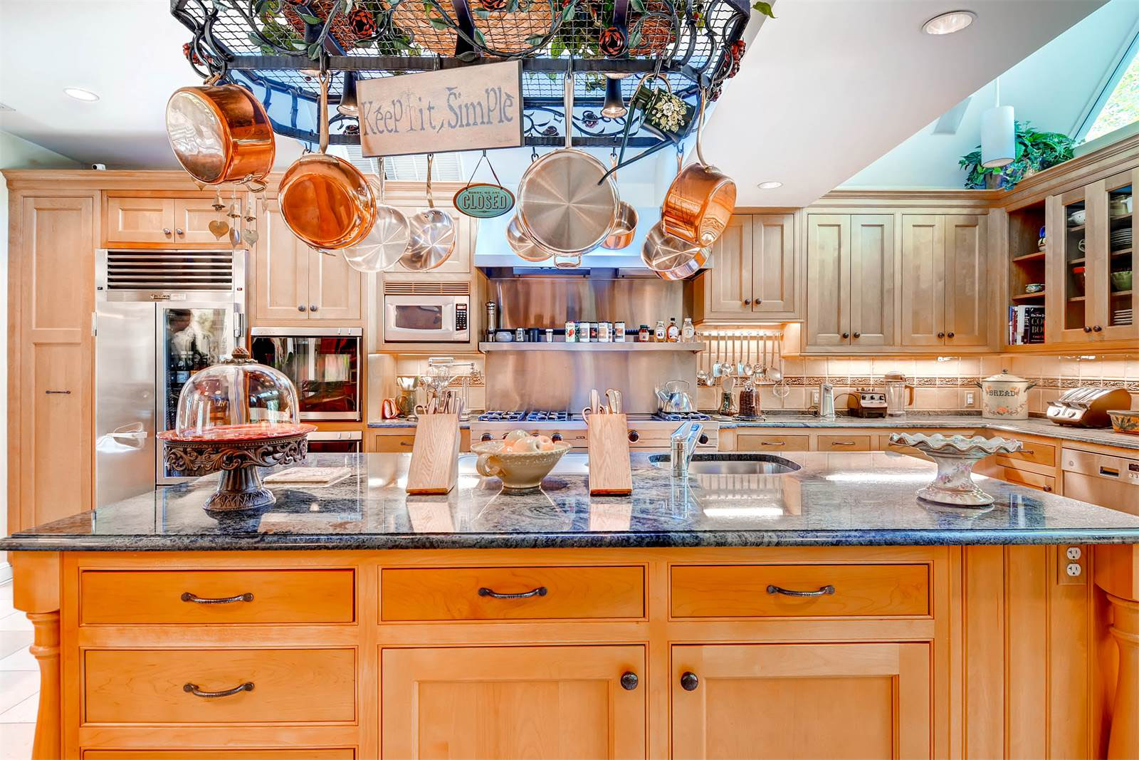 The estate features a gourmet kitchen with center island, off the formal dining room. A separate breaksfast room sits nearby. (Courtesy Monument Sotheby's International Realty)