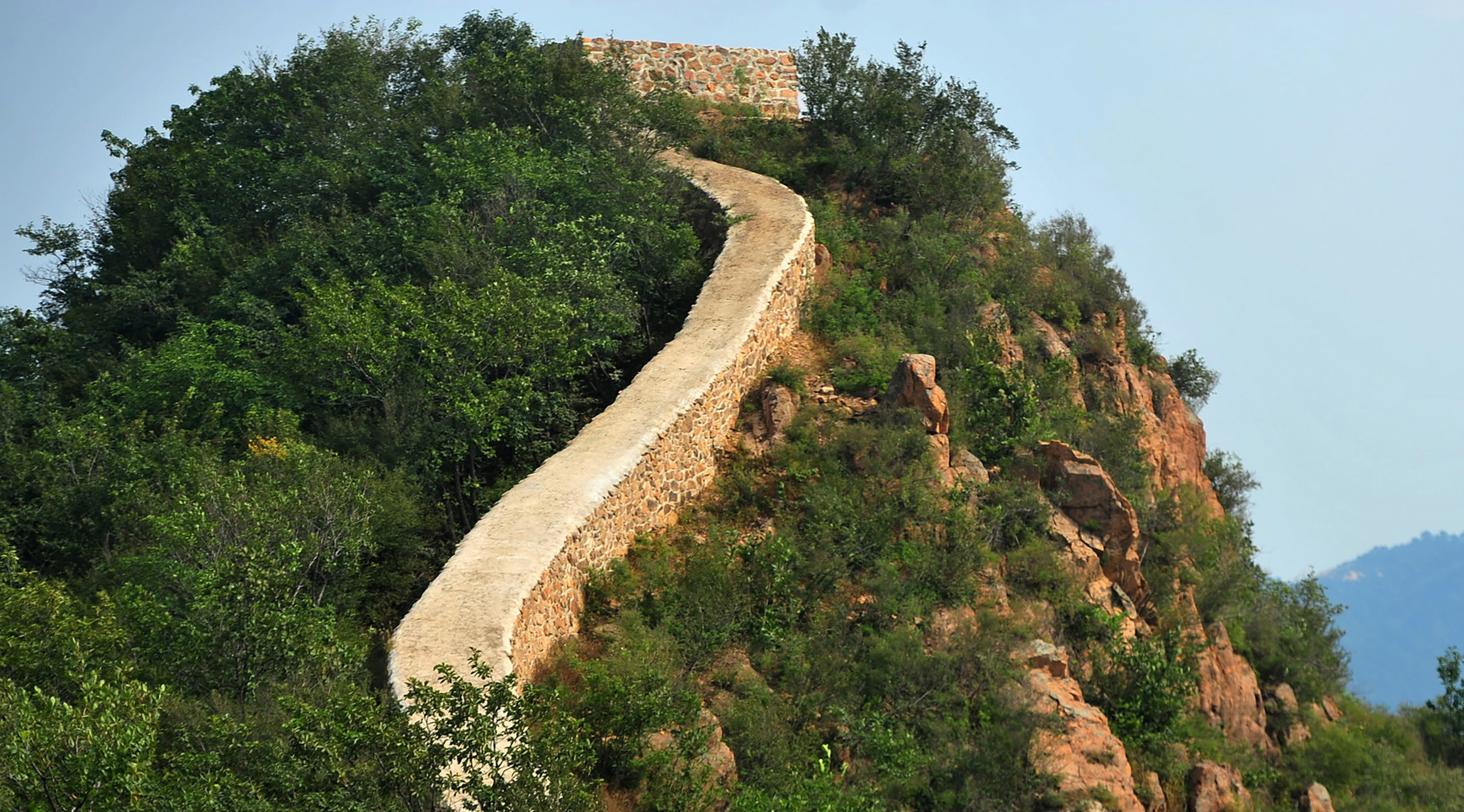 In this Wednesday, Sept. 21, 2016, photo, a restored section of the Great Wall is seen in Suizhong County in northeastern China's Liaoning Province. Chinese officials are being pilloried over the smoothing-over of a crumbling but much-loved 700-year-old section of the Great Wall of China - a UNESCO World Heritage Site - in the name of restoration. (Chinatopix via AP)