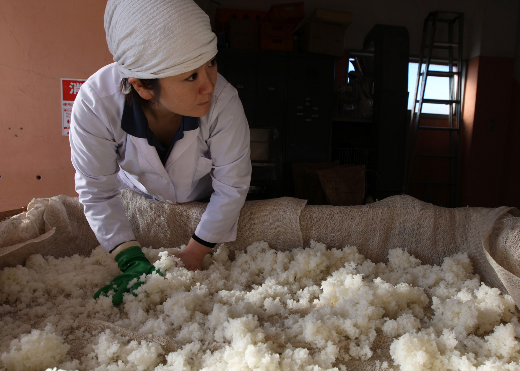 HIMEJI, JAPAN - NOVEMBER 16:  Misa Kawaisi, chief sake brew master, cools steamed rice at Nadagiku-Shozo sake brewery on November 16, 2012 in Himeji, Japan. Kawaishi, one of a few female sake brew masters, is a unique figure in male-diminated sake brewers world.  (Photo by Buddhika Weerasinghe/Getty Images)