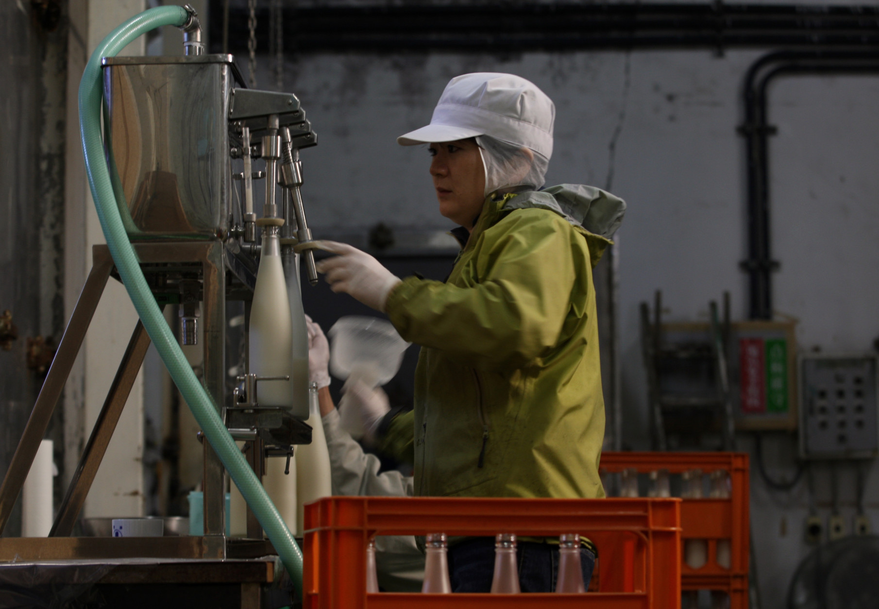 HIMEJI, JAPAN - NOVEMBER 16:  Misa Kawaisi, chief sake brew master, fills sake bottles at Nadagiku-Shozo sake brewery on November 16, 2012 in Himeji, Japan. Kawaishi, one of a few female sake brew masters, is a unique figure in male-diminated sake brewers world. (Photo by Buddhika Weerasinghe/Getty Images)