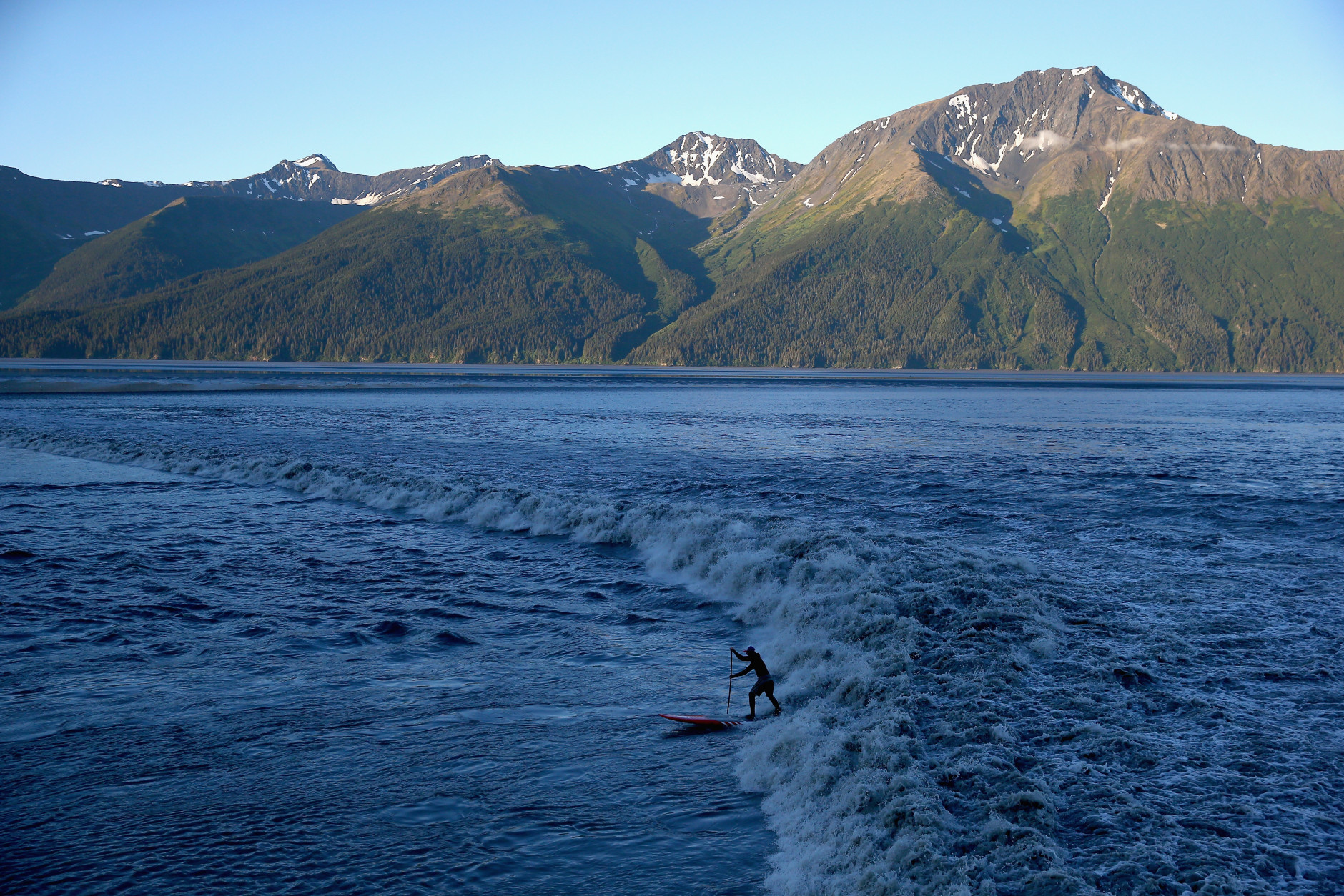 ANCHORAGE, AK - JULY 14:  A surfer rides the Bore Tide at Turnagain Arm on July 14, 2014 in Anchorage, Alaska. Alaska's most famous Bore Tide, occurs in a spot on the outside of Anchorage in the lower arm of the Cook Inlet, Turnagain Arm, where wave heights can reach 6-10 feet tall, move at 10-15 mph and the water temperature stays around 40 degrees Fahrenheit. This years Supermoon substantially increased the size of the normal wave and made it a destination for surfers.  (Photo by Streeter Lecka/Getty Images)
