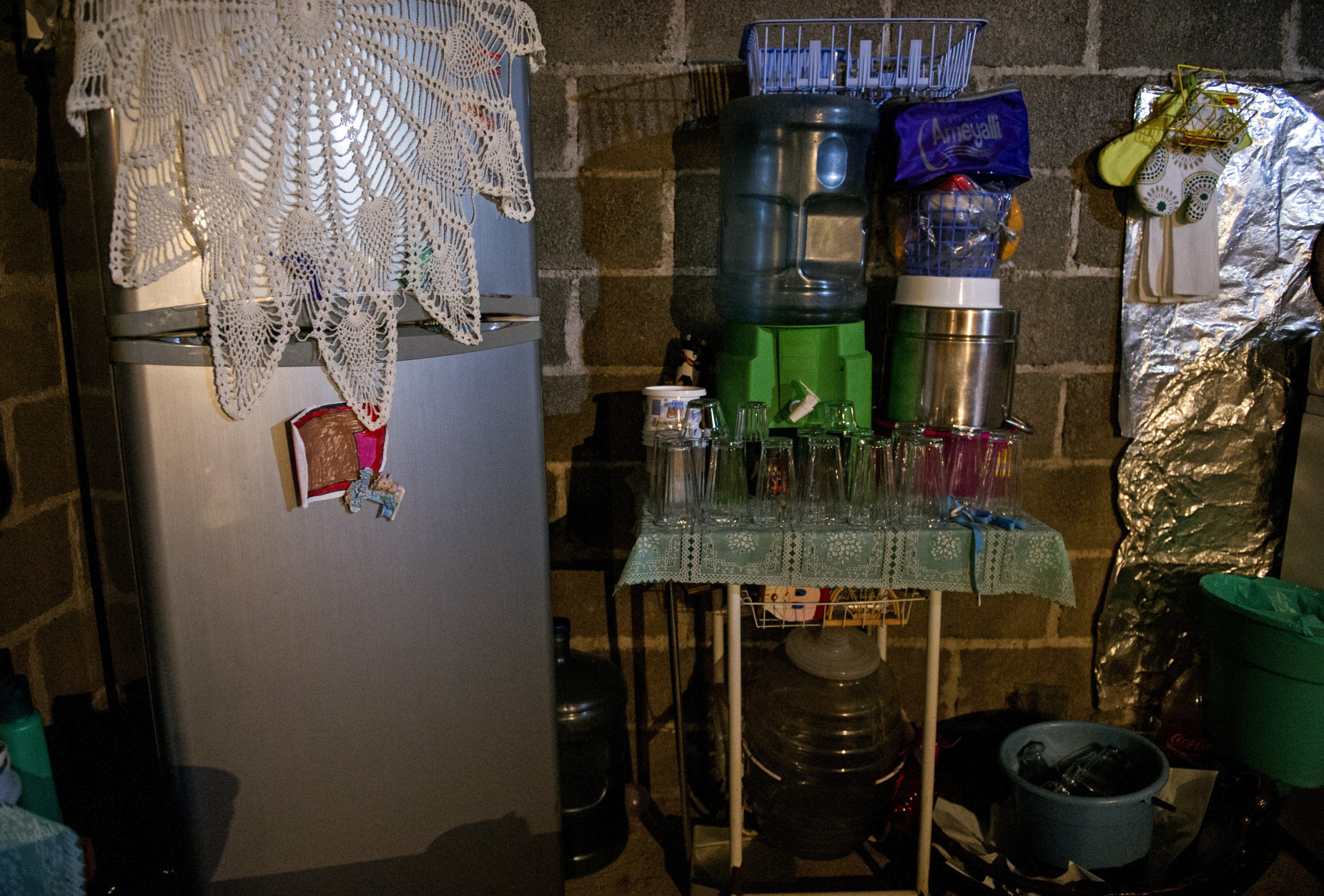 This Aug. 22, 2016 photo shows Edgar Serralde's kitchen, with a small table supporting a counter top water dispenser and drinking glasses, in Mexico City's borough Xochimilco. Like roughly one million Mexico City residents, Serralde isn't on the city's water system. Instead of relying on water trucks Serralde built his one-bedroom house with an intentionally slanted roof, creating a makeshift rain harvesting system. (AP Photo/Nick Wagner)