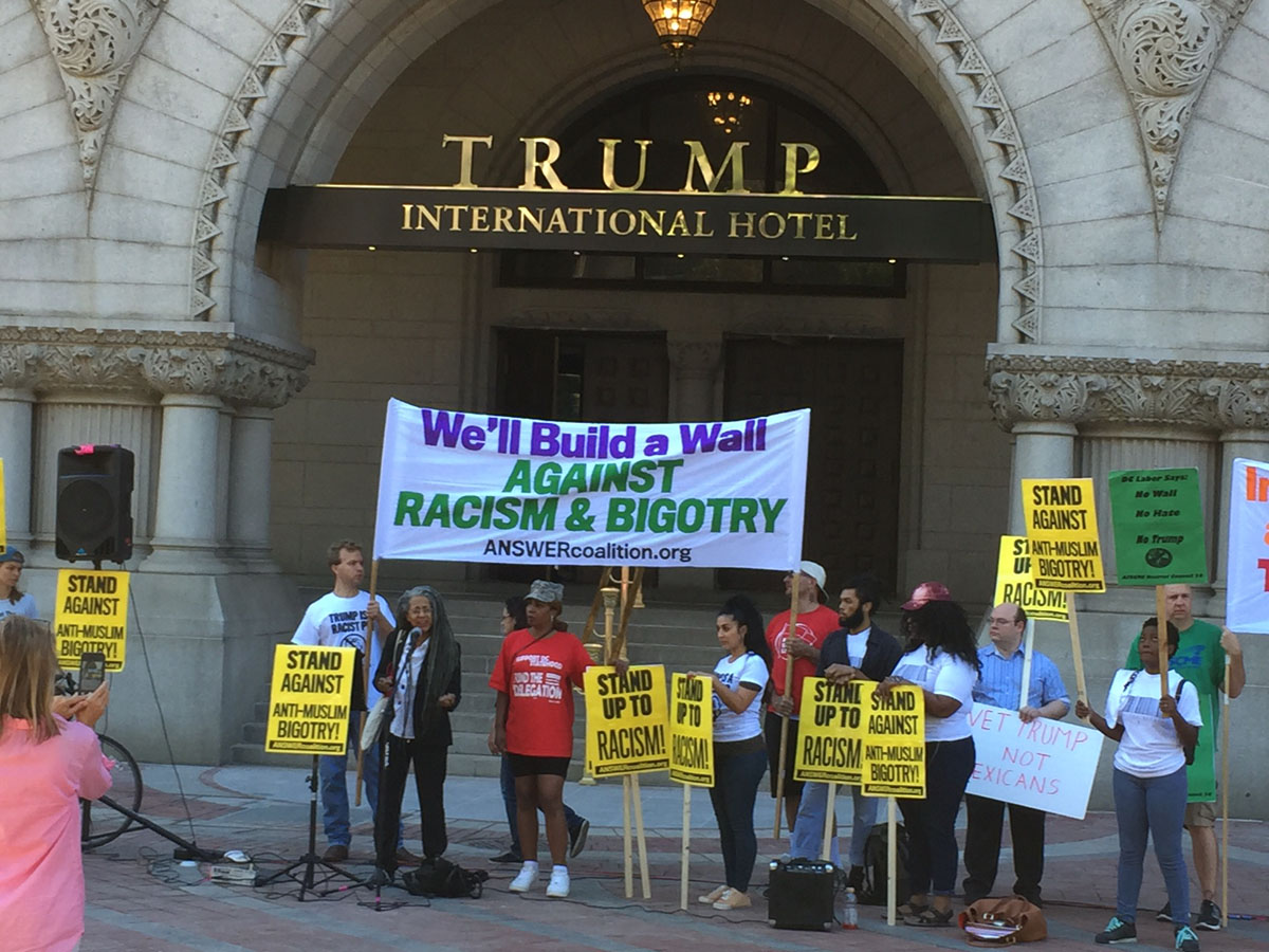 """Protesters outside the Trump International Hotel on Pennsylvania Avenue in D.C. The hotel held a """"soft opening"""" on Sept. 12. The Trump Organization won a 60-year lease from the federal government to transform the Old Post Office building into a hotel. (WTOP photo/Rich Johnson)"""