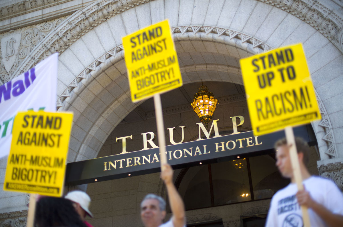 """Demonstrators stand outside the Trump International Hotel during it's 'soft-opening' in downtown Washington, Monday, Sept. 12, 2016 in Washington. The luxury hotel Donald Trump has built in an iconic downtown Washington building is set to open. The Trump International Hotel will begin serving guests Monday. There won't be any fanfare around the opening, which is known as a """"soft opening."""" Grand-opening ceremonies are being planned for October. The Trump Organization won a 60-year lease from the federal government to transform the Old Post Office building on Pennsylvania Avenue into a hotel. (AP Photo/Pablo Martinez Monsivais)"""