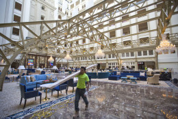 """Workers continue work at the Trump International Hotel during the 'soft-opening' in downtown Washington, Monday, Sept. 12, 2016 in Washington. The luxury hotel Donald Trump has built in an iconic downtown Washington building is set to open. The Trump International Hotel will begin serving guests Monday. There won't be any fanfare around the opening, which is known as a """"soft opening."""" Grand-opening ceremonies are being planned for October. The Trump Organization won a 60-year lease from the federal government to transform the Old Post Office building on Pennsylvania Avenue into a hotel. (AP Photo/Pablo Martinez Monsivais)"""