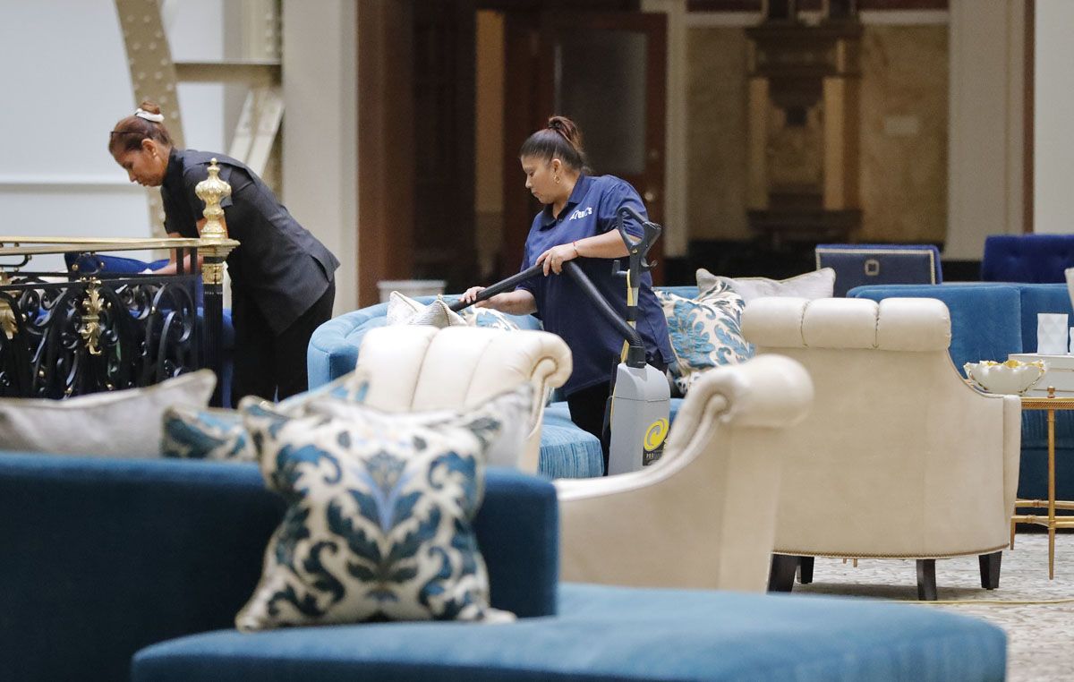 """Workers vacuum furniture in the lobby at the Trump International Hotel in downtown Washington, Monday, Sept. 12, 2016 in Washington. The luxury hotel Donald Trump has built in an iconic downtown Washington building is set to open. The Trump International Hotel will begin serving guests Monday. There won't be any fanfare around the opening, which is known as a """"soft opening."""" Grand-opening ceremonies are being planned for October. The Trump Organization won a 60-year lease from the federal government to transform the Old Post Office building on Pennsylvania Avenue into a hotel. (AP Photo/Pablo Martinez Monsivais)"""
