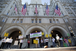 """Demonstrators protests in front of the main entrance to the Trump International Hotel in downtown Washington, Monday, Sept. 12, 2016. The luxury hotel Donald Trump has built in an iconic downtown Washington building is set to open. The Trump International Hotel will begin serving guests Monday. There won't be any fanfare around the opening, which is known as a """"soft opening."""" Grand-opening ceremonies are being planned for October. The Trump Organization won a 60-year lease from the federal government to transform the Old Post Office building on Pennsylvania Avenue into a hotel. (AP Photo/Pablo Martinez Monsivais)"""