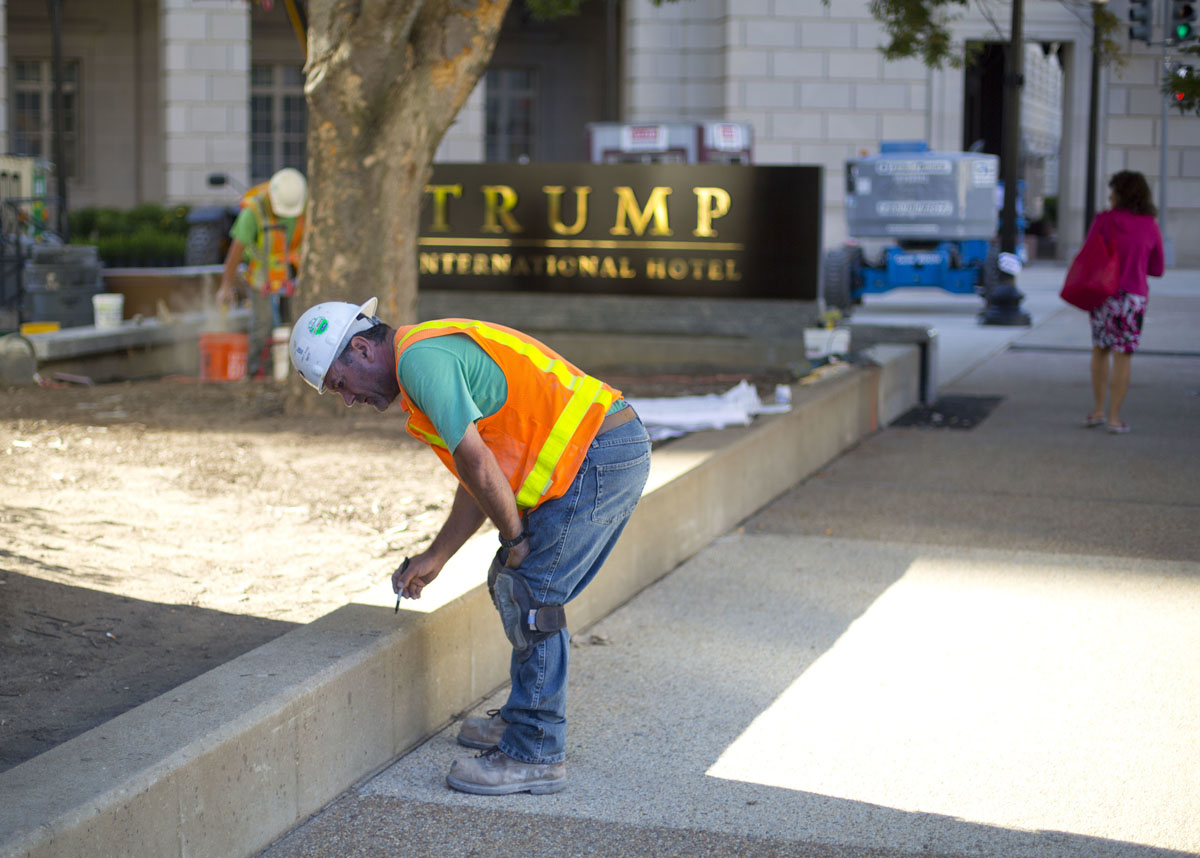 """Workers continue work outside the Trump International Hotel in downtown Washington, Monday, Sept. 12, 2016. The luxury hotel Donald Trump has built in an iconic downtown Washington building is set to open. The Trump International Hotel will begin serving guests Monday. There won't be any fanfare around the opening, which is known as a """"soft opening."""" Grand-opening ceremonies are being planned for October. The Trump Organization won a 60-year lease from the federal government to transform the Old Post Office building on Pennsylvania Avenue into a hotel. (AP Photo/Pablo Martinez Monsivais)"""