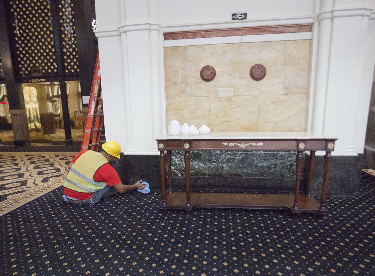 """A worker cleans the marble in the lobby of the Trump International Hotel in downtown Washington, Monday, Sept. 12, 2016 in Washington. The luxury hotel Donald Trump has built in an iconic downtown Washington building is set to open. The Trump International Hotel will begin serving guests Monday. There won't be any fanfare around the opening, which is known as a """"soft opening."""" Grand-opening ceremonies are being planned for October. The Trump Organization won a 60-year lease from the federal government to transform the Old Post Office building on Pennsylvania Avenue into a hotel. (AP Photo/Pablo Martinez Monsivais)"""