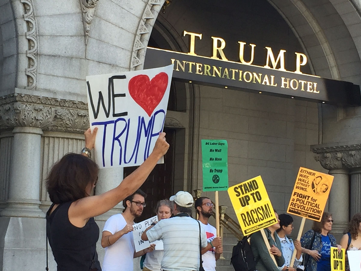 """A counter-demonstrator outside the Trump International Hotel on Pennsylvania Avenue in D.C. The hotel held a """"soft opening"""" on Sept. 12. The Trump Organization won a 60-year lease from the federal government to transform the Old Post Office building into a hotel. (WTOP photo/Rich Johnson)"""
