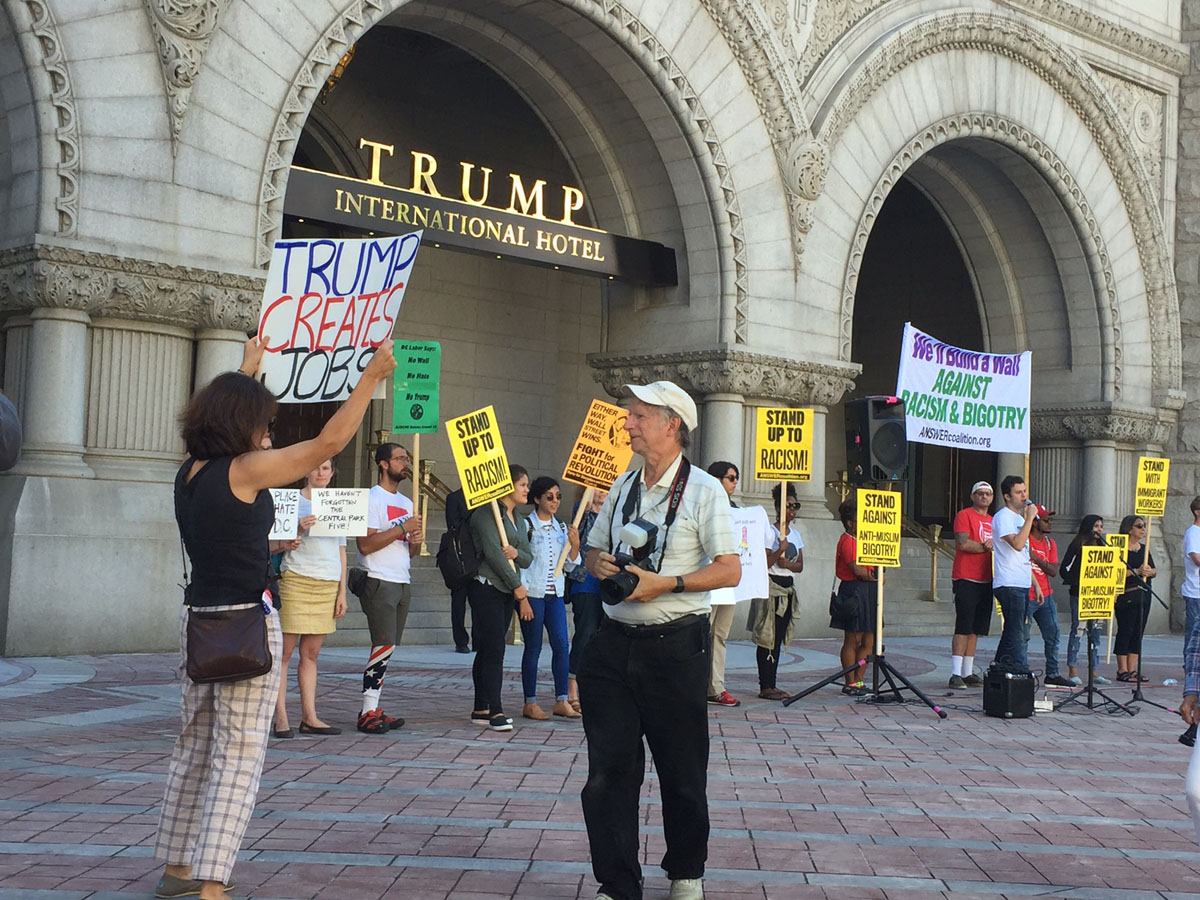 """A counter-demonstrater outside the Trump International Hotel on Pennsylvania Avenue in D.C. The hotel held a """"soft opening"""" on Sept. 12. The Trump Organization won a 60-year lease from the federal government to transform the Old Post Office building into a hotel. (WTOP photo/Rich Johnson)"""