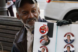 """Steven Plummer was selling campaign buttons outside the Trump Hotel Oct. 26. He had his bases covered: with both Donald Trump and Hillary Clinton buttons available. With a smile, he said """"For this particular crowd, we sold ...more Dump Trump buttons!"""" (WTOP/Kate Ryan)"""