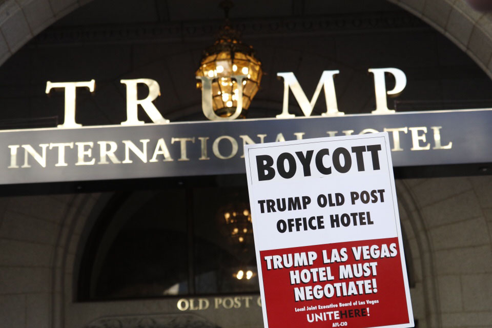 A protester holds up a sign at the Trump Interational Hotel opening Oct. 26. (WTOP/Kate Ryan)