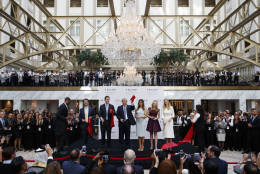 Republican presidential candidate Donald Trump, accompanied by, from left, Donald Trump Jr., Eric Trump, Trump, Melania Trump, Tiffany Trump and Ivanka Trump, holds up a ribbon during the grand opening ceremony of the Trump International Hotel- Old Post Office, Wednesday, Oct. 26, 2016, in Washington. (AP Photo/ Evan Vucci)