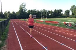 """Roxanne trains for the Marine Corps Marathon on the track at George Mason High School, trying to finally fulfill her son's dream of finishing the MCM with a fast enough time to qualify for the Boston Marathon. """"That definitely would be on the wings of Jeff,"""" she said. (Courtesy Roxanne Kaylor)"""