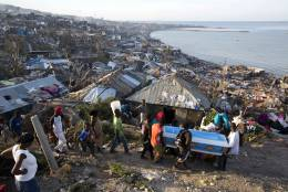 Residents carry a coffin containing the remains of a pregnant woman, a victim of Hurricane Matthew, in Jeremie, Haiti. Friday, Oct. 7, 2016. People across southwest Haiti were digging through the wreckage of their homes Friday, salvaging what they could of their meager possessions after Matthew killed hundreds of people in the impoverished country. (AP Photo/Dieu Nalio Chery)