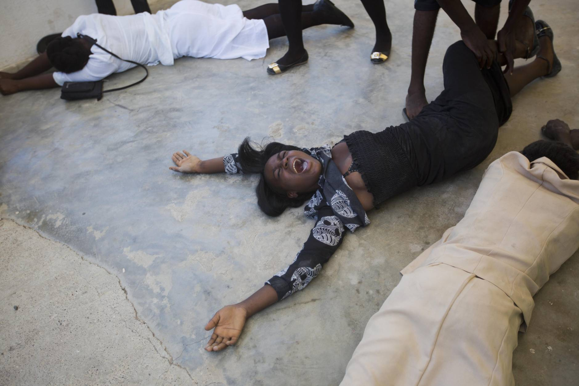 Women from the Laguerre family cry as the coffin carrying Roberto Laguerre is taken out of the morgue, to bury him at the cemetery in Jeremie, Haiti, Saturday Oct. 8, 2016. Roberto, 32, died when the wall of a church next door to his home fell during Hurricane Matthew. (AP Photo/Dieu Nalio Chery)