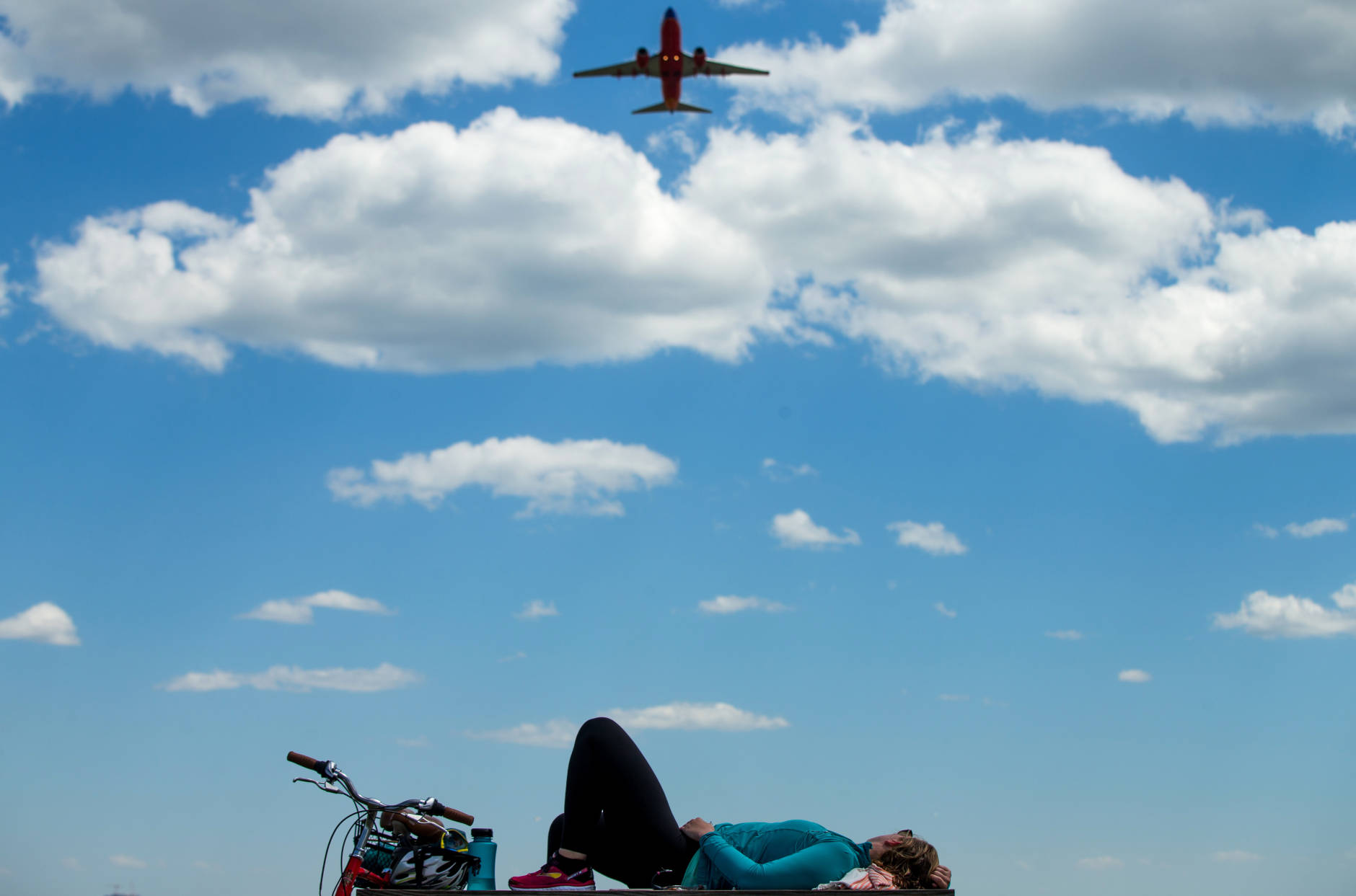 A plane takes off from Washington's Ronald Reagan National Airport as Julia Hurley of Washington relaxes on a picnic table at Gravelly Point Park in Arlington, Va., Wednesday, June 8, 2016, after bicycling to Mt. Vernon and back. (AP Photo/Andrew Harnik)