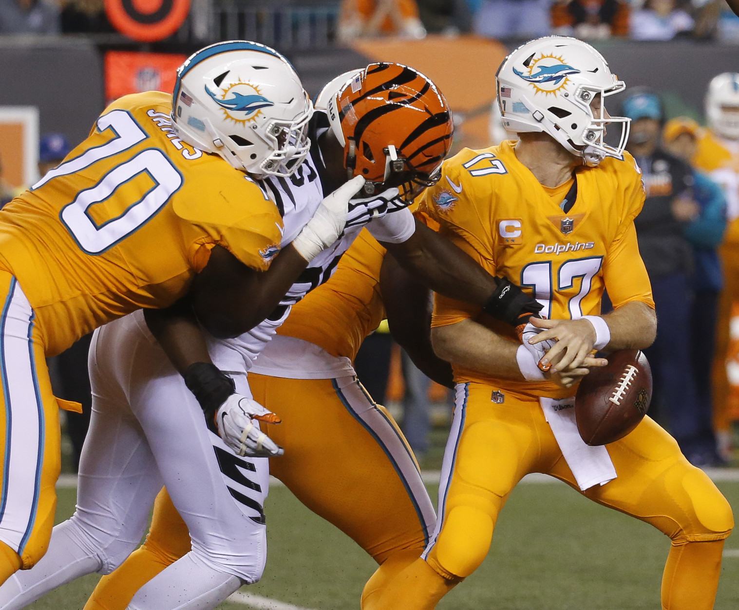 Cincinnati Bengals defensive end Carlos Dunlap, second from left, forces a fumble by Miami Dolphins quarterback Ryan Tannehill, center, in the first half of an NFL football game, Thursday, Sept. 29, 2016, in Cincinnati. The Bengals recovered the fumble. (AP Photo/Frank Victores)