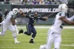 Seattle Seahawks quarterback Russell Wilson (3) runs away from New York Jets' Sheldon Richardson (91) during the second half of an NFL football game Sunday, Oct. 2, 2016, in East Rutherford, N.J.  (AP Photo/Bill Kostroun)