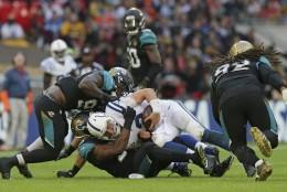 El quarterback Andrew Luck (12), de los Colts de Indianápolis, es capturado por la defensiva de los Jaguars de Jacksonville durante el encuentro en el estadio Wembley de Londres, el domingo 2 de octubre de 2016. (AP Foto/Tim Ireland)