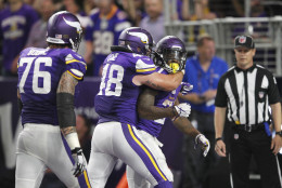 Minnesota Vikings running back Jerick McKinnon, right, celebrates with teammates Zach Line, center, and Alex Boone, left, after scoring on a 4-yard touchdown run during the second half of an NFL football game against the New York Giants Monday, Oct. 3, 2016, in Minneapolis. (AP Photo/Andy Clayton-King)
