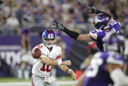 New York Giants quarterback Eli Manning, left, throws a pass around Minnesota Vikings free safety Harrison Smith (22) during the first half of an NFL football game Monday, Oct. 3, 2016, in Minneapolis. (AP Photo/Andy Clayton-King)