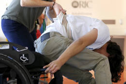 """In this Saturday, Oct. 8, 2016 photo, physical therapist Kat Lowery helps Jonathan Annicks practice a technique for getting back into his wheelchair during a physical therapy session at the Rehabilitation Institute of Chicago. Paralyzed from the chest down by a gunshot wound, his and his families priorities don't include finding the shooter. """"If I lived with spite every day, then I don't think I would be able to function properly,"""" he says. """"I'd be very miserable if I were worrying about what he's doing or where he is. I don't think it's worth it."""" (AP Photo/Charles Rex Arbogast)"""