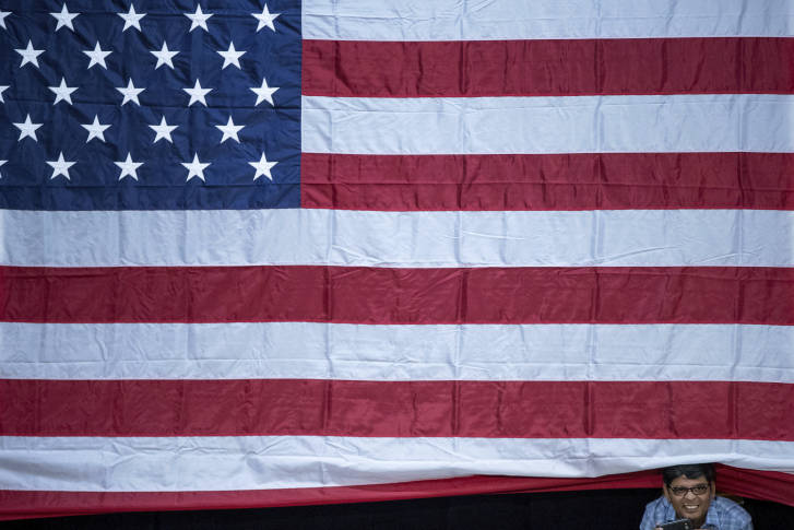 A man sticks his head out from under a large American flag as Democratic  presidential candidate. Hillary Clinton39s Email   jobs4education com