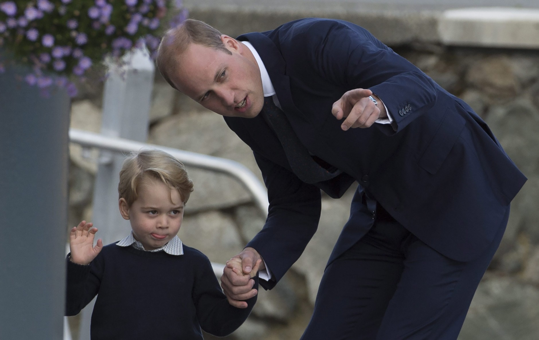 Britain's Prince William, the Duke of Cambridge, and his son, Prince George, wave to the crowd prior to boarding a float plane as they prepare to depart Victoria, British Columbia, Canada, on Saturday, Oct. 1, 2016. (Jonathan Hayward/The Canadian Press via AP)