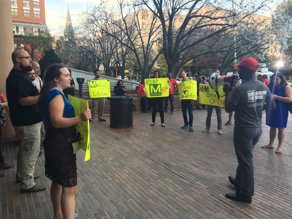 A few people are outside the WMATA HQ holding signs asking to keep Metro open later. (WTOP/Max Smith)