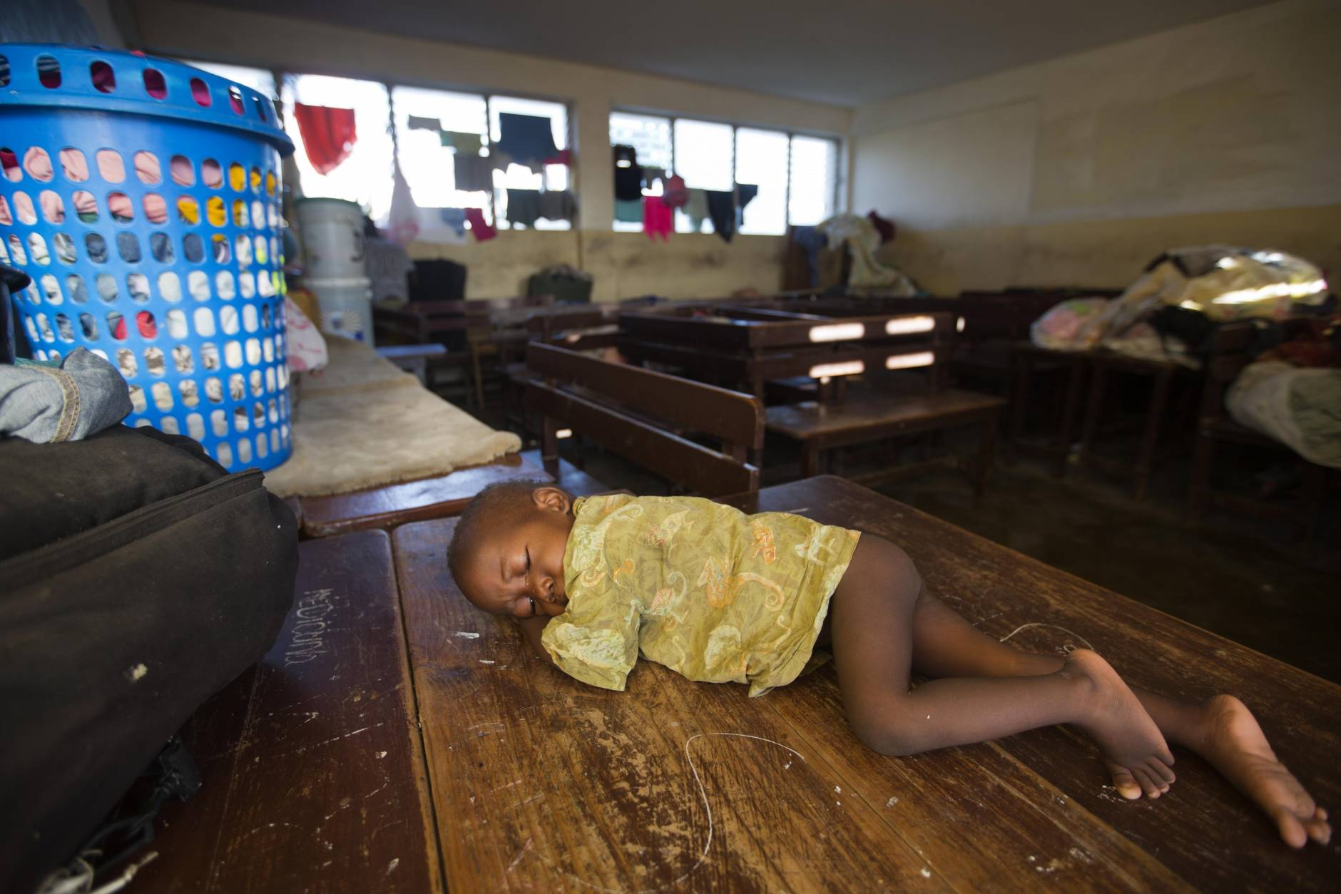 A boy lies on a table in a shelter after Hurricane Matthew passed in Jeremie Haiti,  Saturday Oct. 8, 2016.   Aid has begun pouring into the hard-hit town,  where thousands of homes were damaged or destroyed and many people were running low on food and facing an increased risk for cholera.  ( AP Photo/Dieu Nalio Chery)