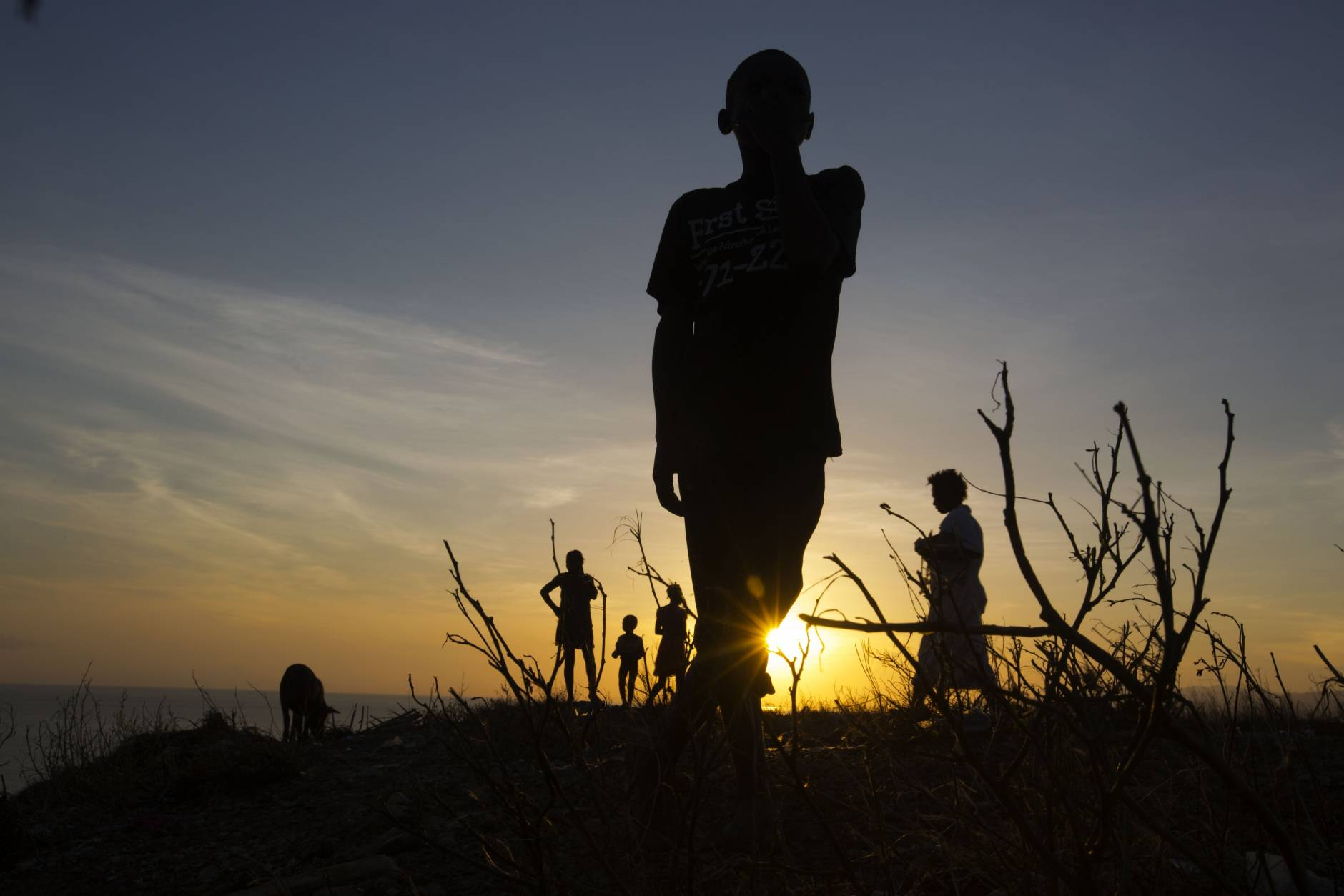 A boy stands on top of the hillside of town of Jeremie, Haiti,  that was destroyed by Hurricane,  Saturday Oct. 8, 2016.  Aid has begun pouring into the hard-hit town,  where thousands of homes were damaged or destroyed and many people were running low on food and facing an increased risk for cholera.  ( AP Photo/Dieu Nalio Chery)