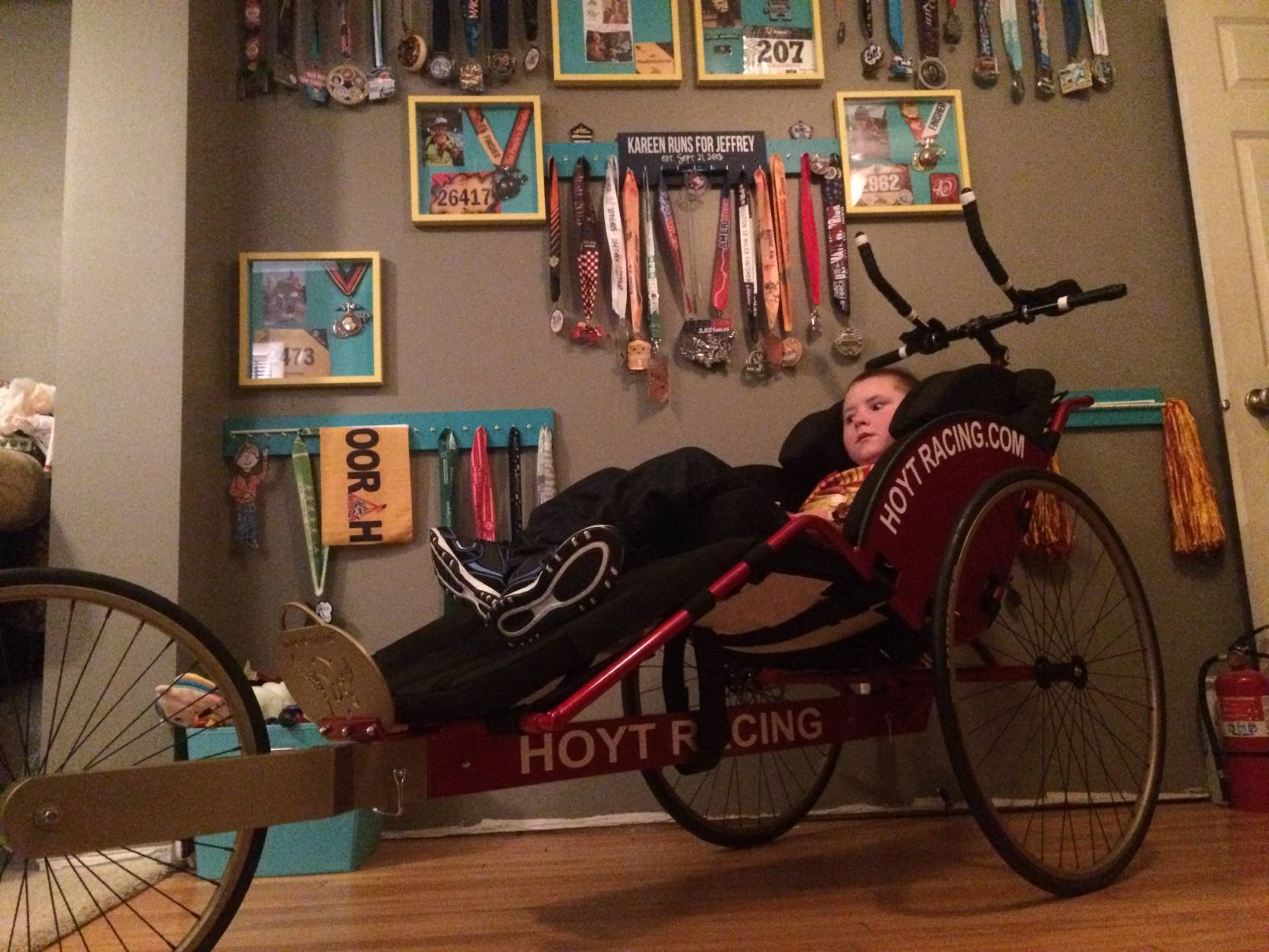 Last year, Kareen and the Bergeman family teamed up with Ainsley's Angels of America ((   http://www.ainsleysangels.org/    ))) and raised enough money to get Jeffrey this new running chair. Because of their fundraising, two children – one from Wisconsin and another in Northern Virginia – will receive a running chair like this one. The wall of his bedroom is covered with Kareen's race medals since they were matched in September 2013. (Courtesy Jess Bergeman)