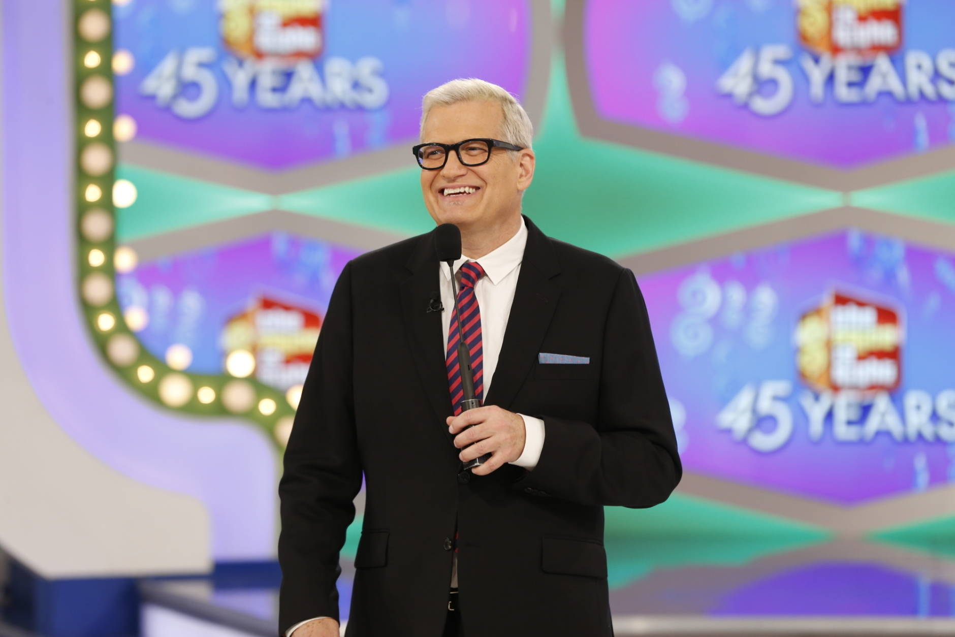 "In this image released by CBS, host Drew Carey appears on the set of ""The Price is Right."" On the episode airing Monday, Oct. 17, 2016, a trio of contestants spun $1 on the game show's famous wheel. The three contestants each landed on different combinations of $1 in a pair of spins during one of the show's showcase showdowns. Carey pumped his fist in the air after the contestants achieved the first three-way tie in the show's history. (Monty Brinton/CBS via AP)"