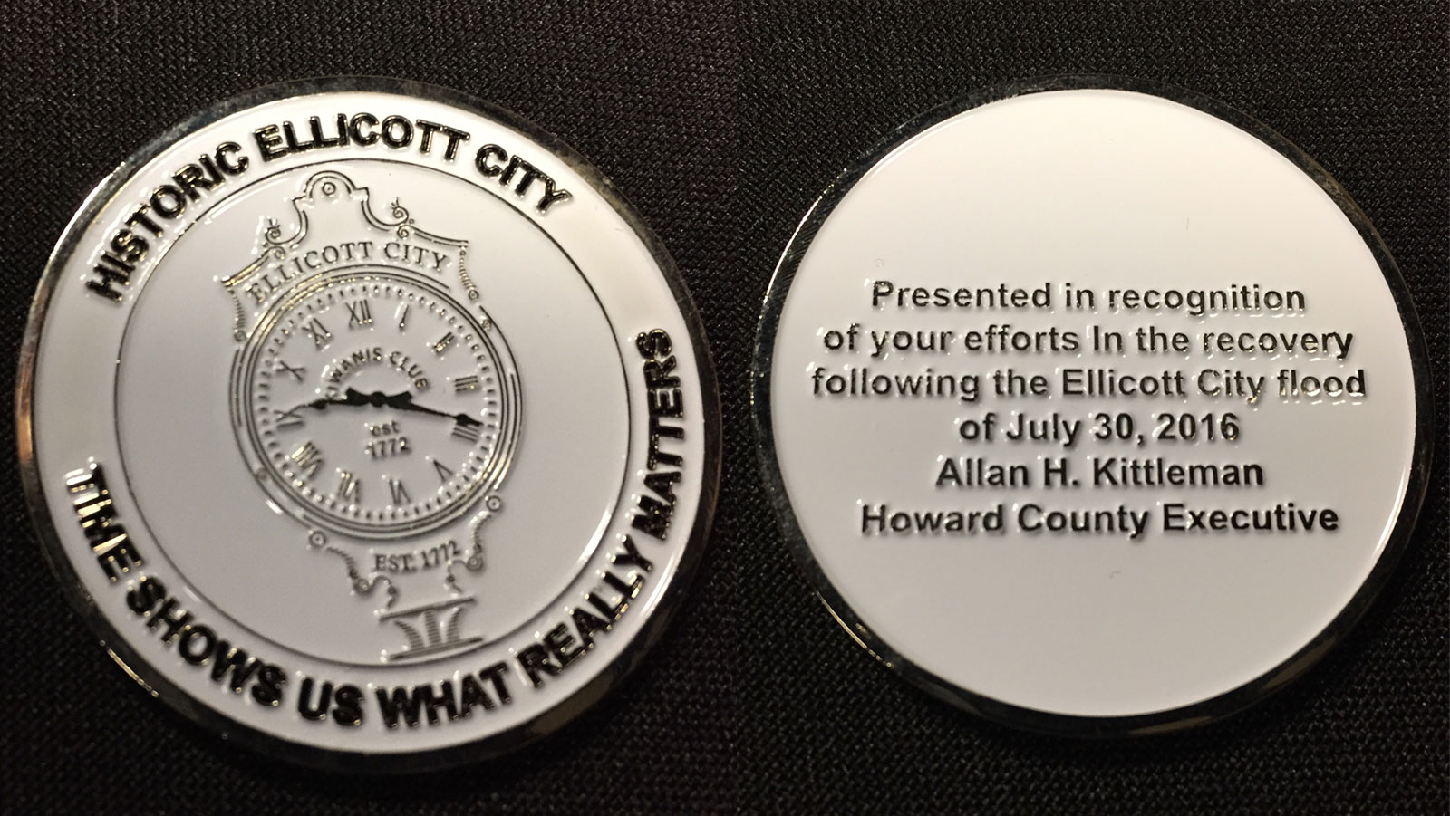 """Each """"flood hero"""" received two coins, including this one, shown with both sides in this photo, from Howard County Executive Allan Kittleman. (WTOP/Michelle Basch)"""