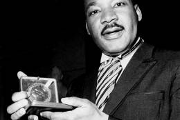 Dr. Martin Luther King, Jr. displays his 1964 Nobel Peace Prize medal in Oslo, Norway, December 10, 1964.  The 35-year-old Dr. King was honored for promoting the principle of non-violence in the civil rights movement.  (AP Photo)