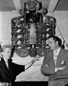 Victoria's parents, Vincent and Mary Price in their Benedict Canyon, Calif., home, with a carving of the African God of Disease which hung over their fireplace,  1950 (AP)