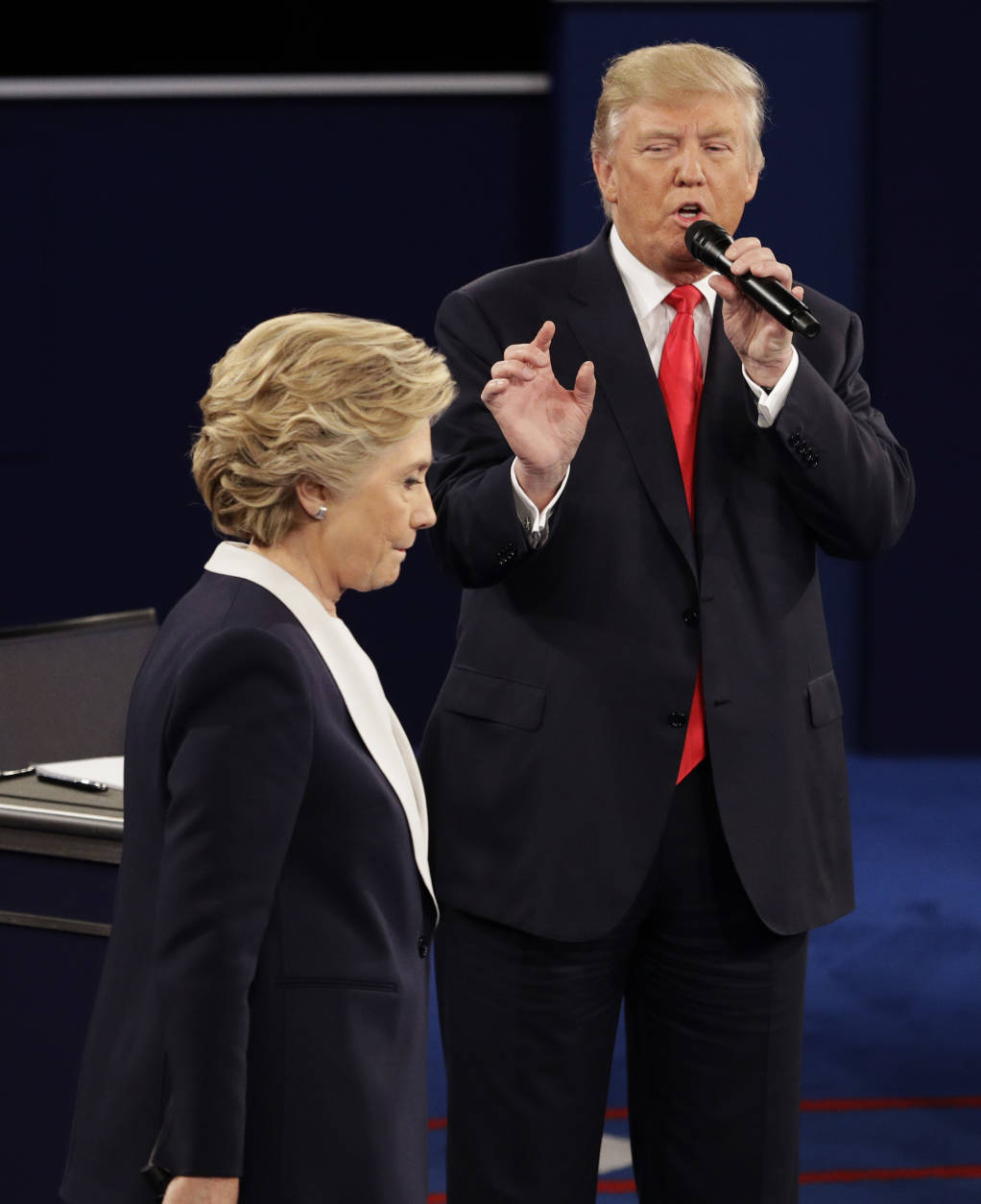 FILE - In this Sunday, Oct. 9, 2016 file photo, Democratic presidential nominee Hillary Clinton walks past Republican presidential nominee Donald Trump during the second presidential debate at Washington University in St. Louis. (AP Photo/John Locher)