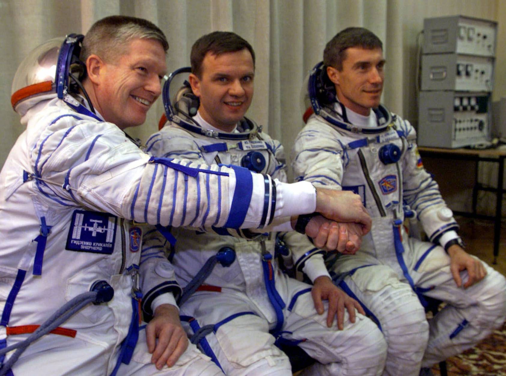 Russian cosmonauts Sergei Krikalyov, right, Yuri Gidzenko and U.S. astronaut Bill Shepherd, left, pose before launching at the Baikonur cosmodrome, Tuesday, Oct. 31, 2000. They became the first residents of the international space station, christening it Alpha on Nov. 2, 2000. (AP Photo/Pool)