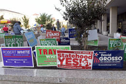 In this photo taken Nov. 3, 2016, signs supporting DC statehood are on display outside an early voting place on in Washington, Thursday, Nov. 3, 2016. Voters in the nation's capital will decide next week whether they want their city to become the nation's 51st state. The referendum backed by Democratic Mayor Muriel Bowser is expected to pass easily. But even staunch statehood supporters say they're not sure of the path forward. (AP Photo/Susan Walsh)