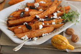 This Oct. 12, 2015, photo shows cider-glazed sweet potatoes with fried sage, garlic and goat cheese in Concord, N.H. (AP Photo/Matthew Mead)