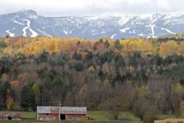 FILE-In this Oct. 18, 2010, file photo, sunlight falls on remaining bright foliage as the snow capped ski trails of Stowe ski resort are seen on the side of Mt. Mansfield in Stowe , Vt. Mountain and lake views along with fall foliage can be had for free in Vermont's largest city of Burlington, which feels more like a big town than a city. (AP Photo/Toby Talbot)