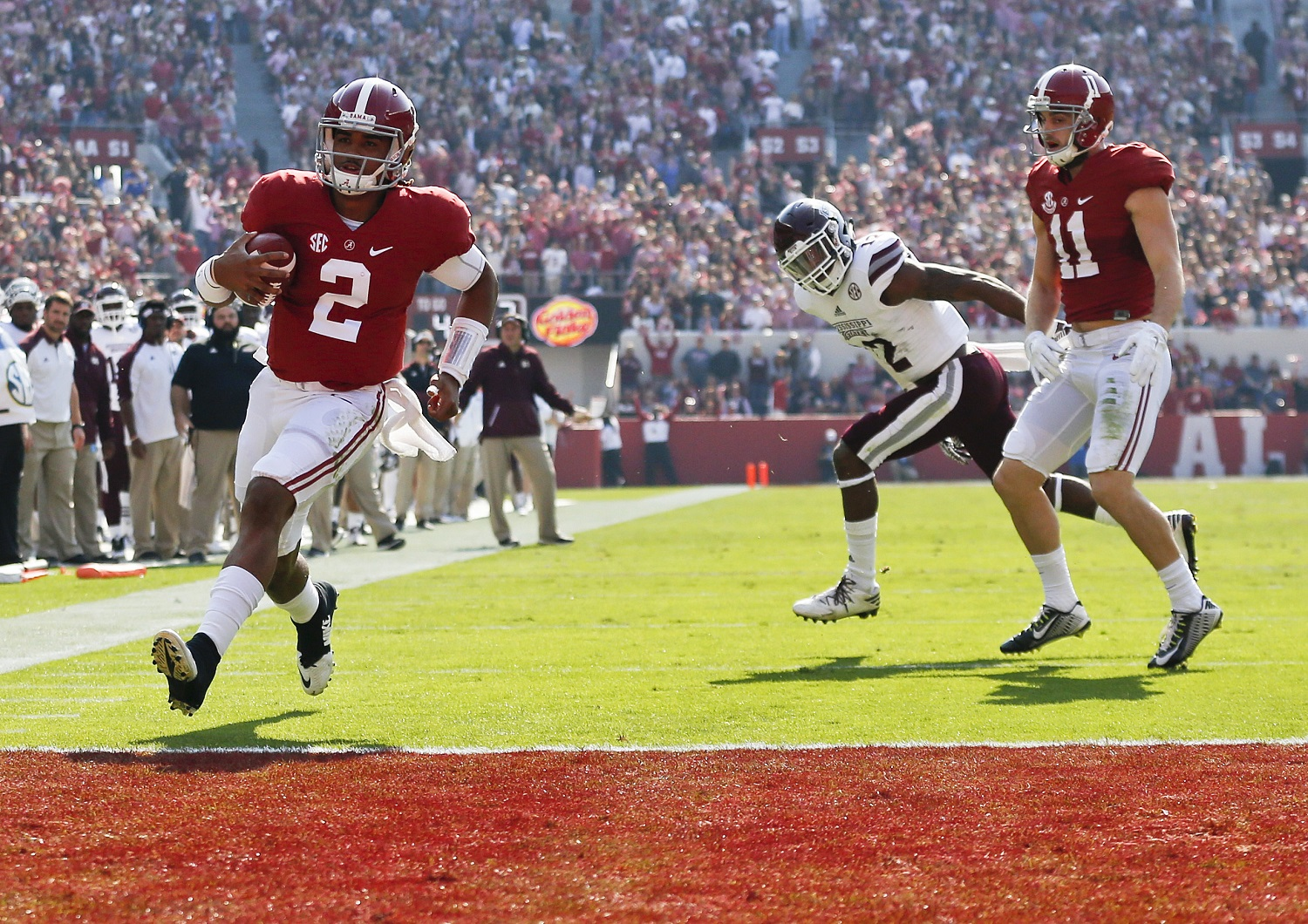 Alabama quarterback Jalen Hurts, left, scores a touchdown during the first half of an NCAA college football game against Mississippi State, Saturday, Nov. 12, 2016, in Tuscaloosa, Ala. (AP Photo/Brynn Anderson)