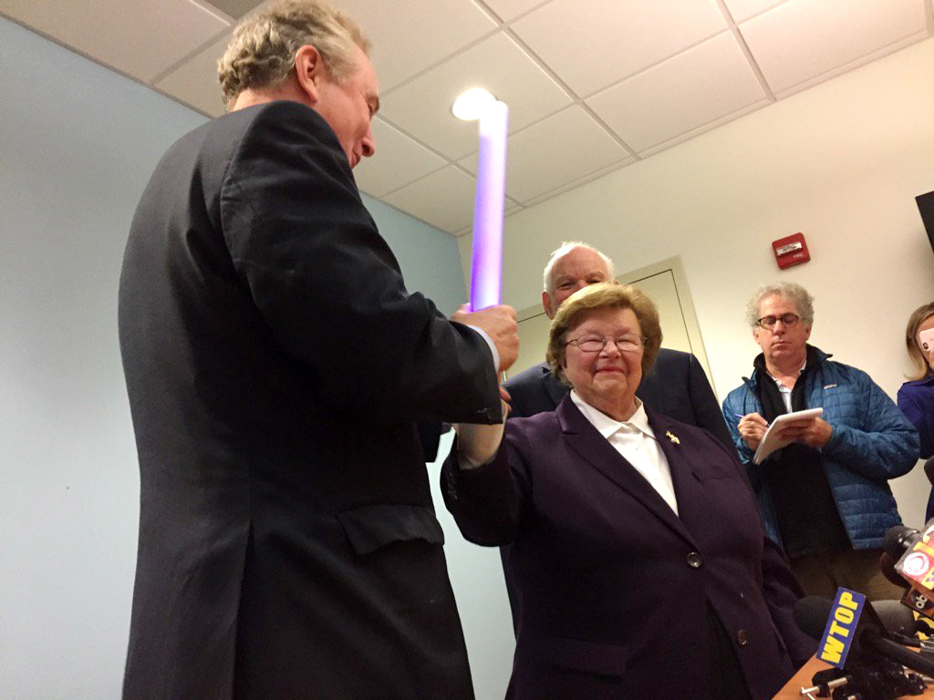 Sen. Barbara Mikulski, the longest-serving woman in the history of Congress, passes the torch  -  a multicolored, flashing, battery-powered light bar - to her successor Chris Van Hollen on Wednesday morning in Baltimore  after her traditional post-electionb breakfast at an eatery near her Baltimore office. (WTOP/John Aaron)